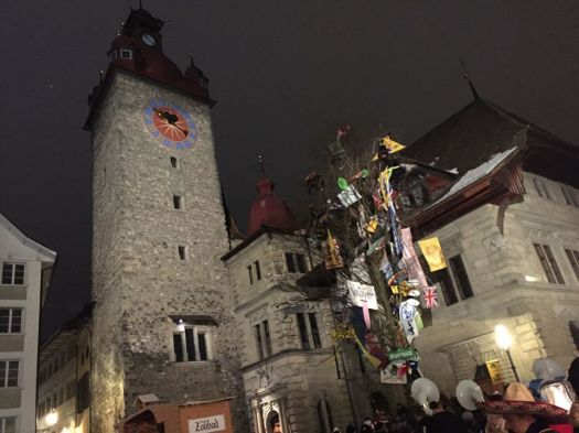 This tree in Lucerne's Old City is festooned with banners from many Guggenmusik ensembles for Fasnacht. How did they get all those banners into the tree????